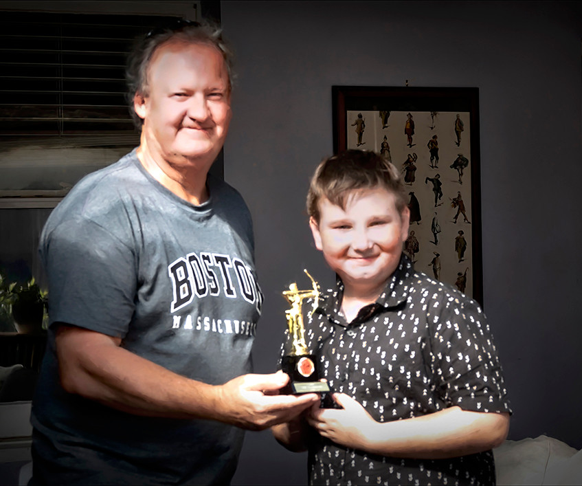 Graham presenting Mathew Robinson with his award as Club Champion in the Cub Male Compound Division.