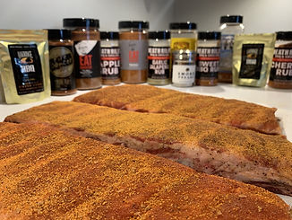 10	Seasoned spare ribs next to shakers of rubs from BBQ Pro Shop
