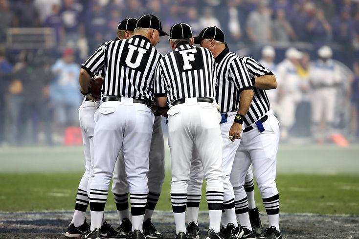 Bild von fünf Schiedszrichtern beim Footballspiel die sich beraten.