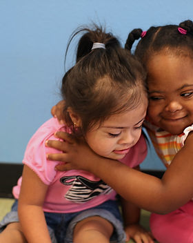 Two children with disabilities hugging each other