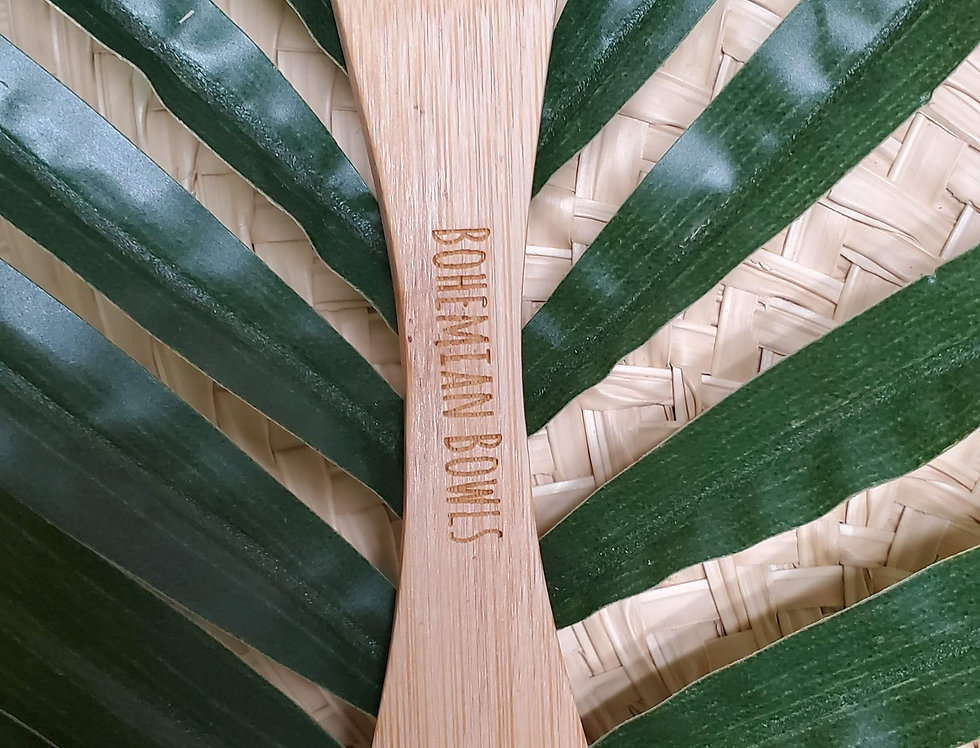 Bohemian Bowls Bamboo Spork Laying On Top Of Palm Leaf And Straw Mat