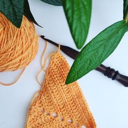 orange-gold yarn on a crochet hook