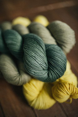 dark green and yellow skeins of yarn