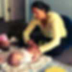 Mother performing infant massage strokes at group infant massage class