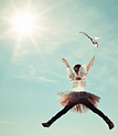 Young girl dressed as a fairy leaping for joy