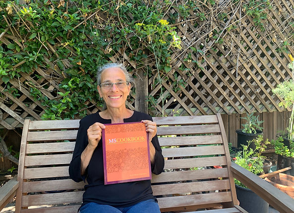 The author of the cookbook, Raquel Pinderhughes, holds the cookbook sitting on a bench in her garden