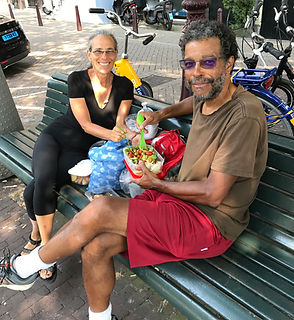 Image of the author Raquel Pinderhughes, and her husband Howard eating a delicious lunch on a bench