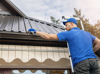 man standing on ladder and cleaning roof