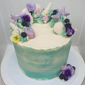 Mermaid themed cake with mermaid tails and seashells