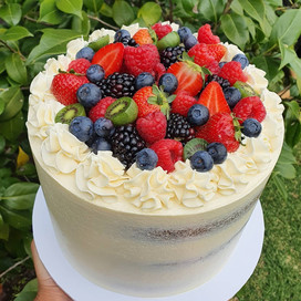 Medium Tall Pavlova style cake, with berries and layers of passionfruit curd