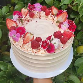 Small vanilla cake white cake textured with pink theme berries and edible flowers