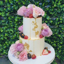 Two Tiered Coconut & Raspberry Cake with Caramel drip, Gold leaf Berries with gold dusting   and fresh pink flowers.