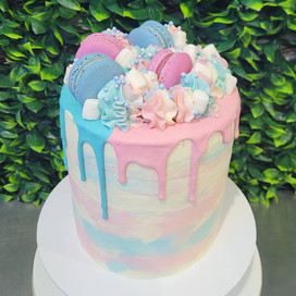 Medium slim Gender reveal Vanilla with Blue+pink watercolour icing & drip,with blue +pink macarons, icing swirls, sprinkles and mini marshmallows.