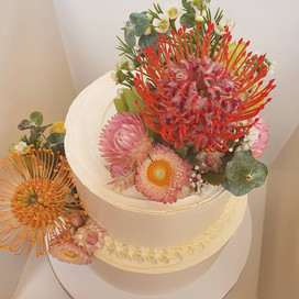 Two Tiered medium size carrot cake with native  flowers
