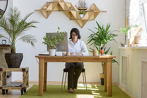 Woman sitting at desk in relaxing space for vastu consultations