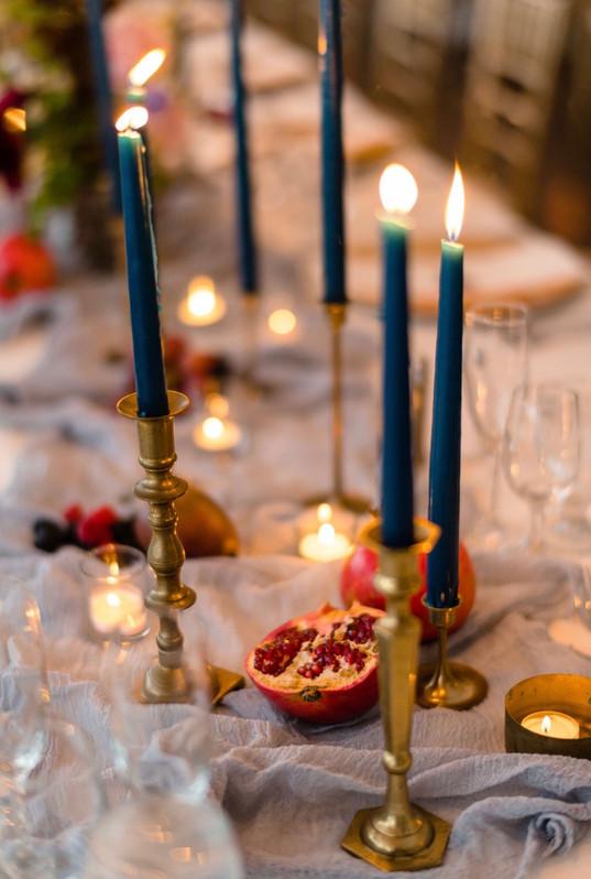 samara_floral_wedding_flowers_centerpiece_arrangement_moody_art_ranunculus_colorful_reception_taper_candles_fruit