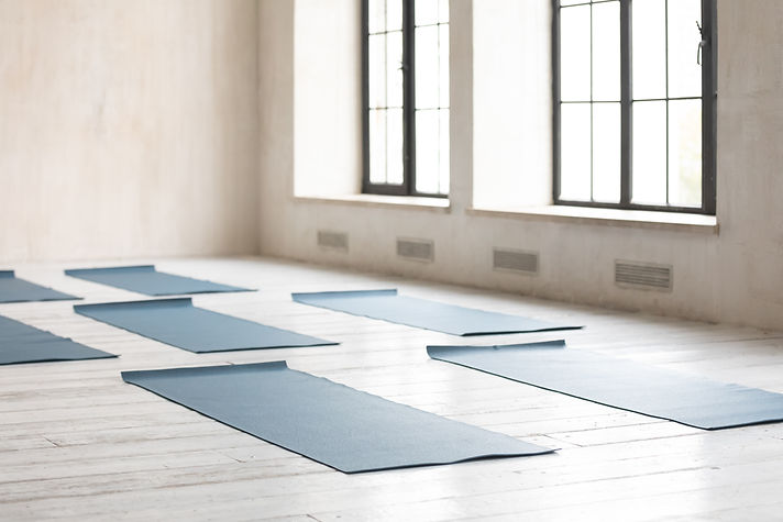 Unrolled yoga mats on wooden floor in fi
