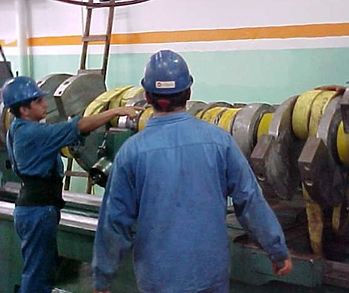 workers in front of crankshaft and counter weights