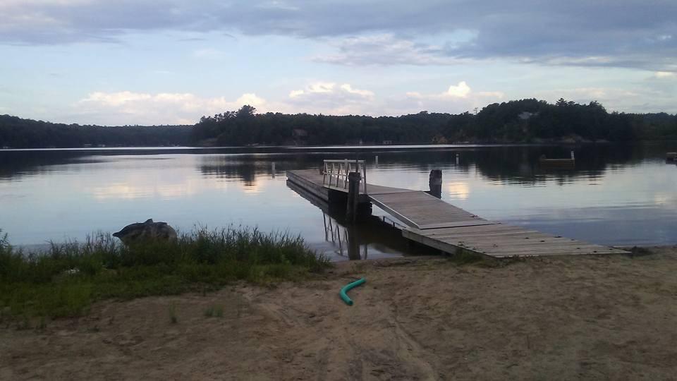 un quai se jette dans un lac alors que les nuages se reflètent à la surface
