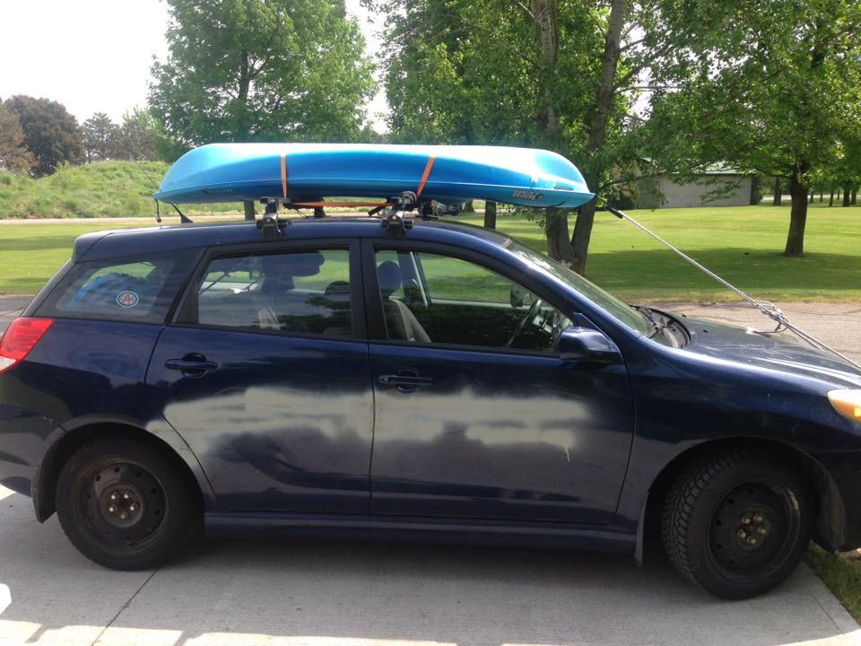 Blue Toyota Matrix with a kayak strapped to the roofracks