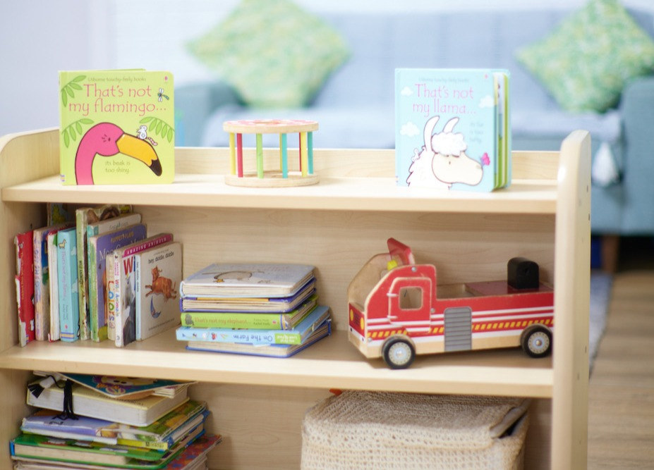 Bookshelf with books and toys with sofa in background