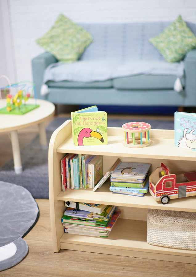 Bookshelf with toys, sofa and coffee table in background
