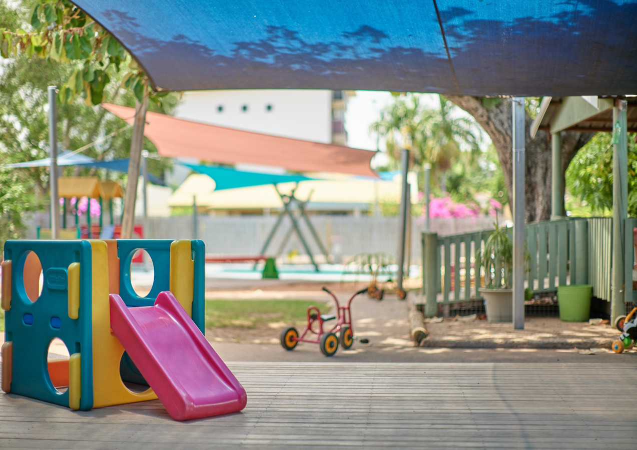 Toddler slide on deck with trike and swing in background