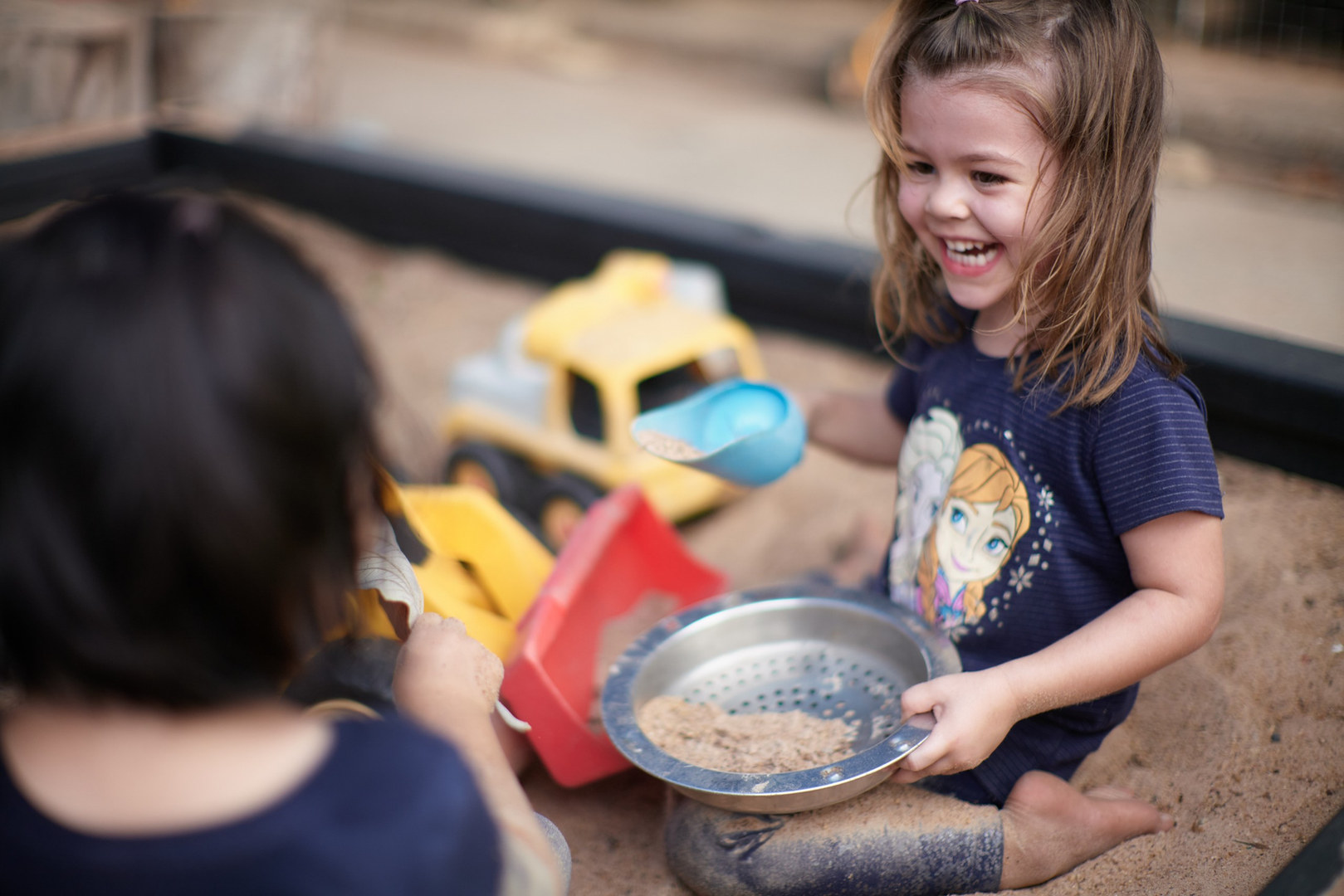 Two girls laughing, having fun, playing in sandpit