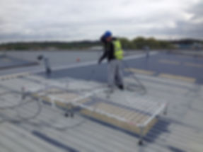 Man working on fragile roof surface with safety protection roof net