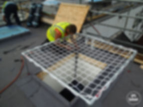 Man woring on open roof skylight with safety net quadtube fall protection SPS Safenet