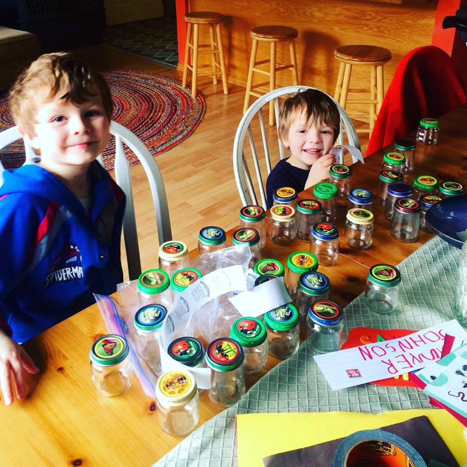 Boys working on stickering the bug collecting jars.