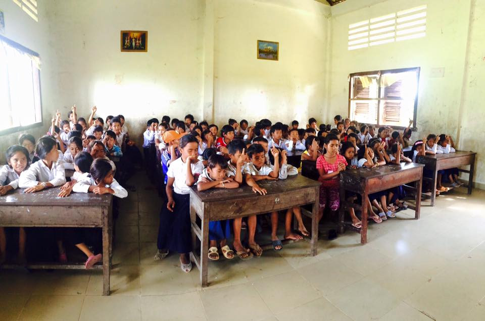 Students from a public school raising their hands to receive Christ
