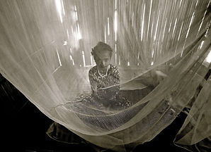 Photo by photographer Pearl Gan showing young child in Indonesia sitting in a mosquito net