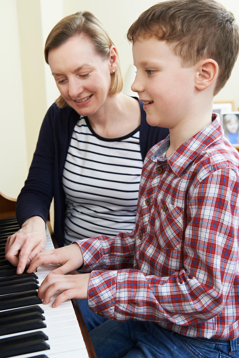 A teacher helps a student learn to play the piano in his lesson