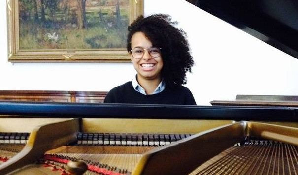 Bailey Grineage, piano teacher at Upper Beaches Music School in East Toronto, smiles at the piano
