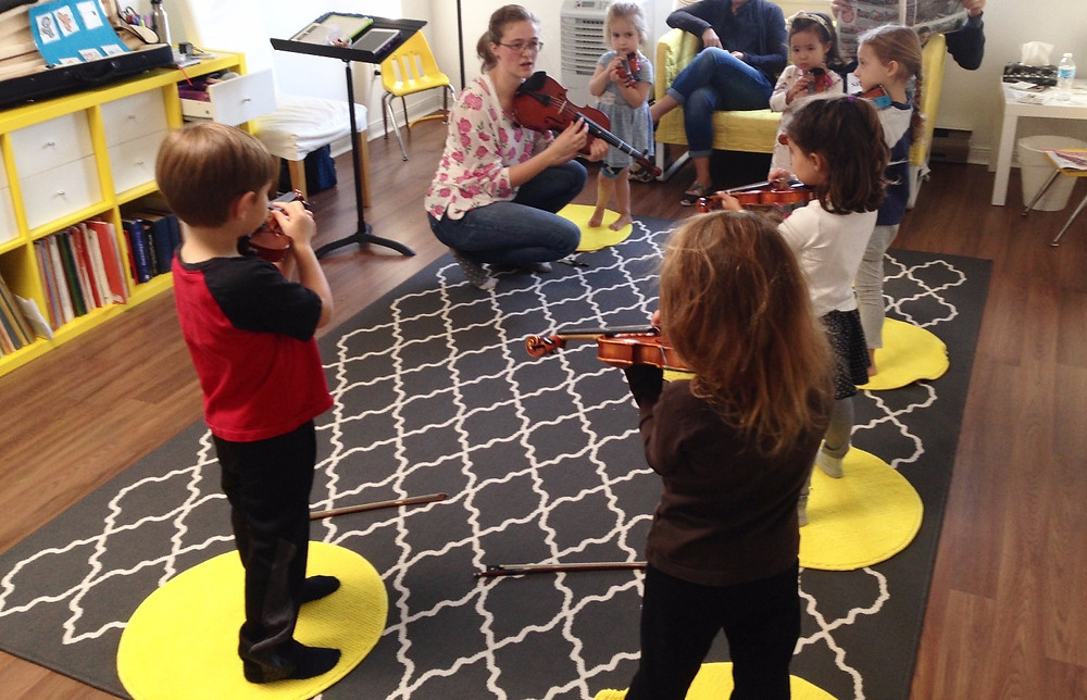 Children playing violin with music teacher in a Suzuki group class at Upper Beaches Music School in east Toronto on Danforth