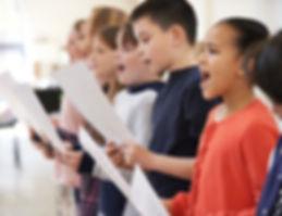 Group Of School Children Singing In Choi