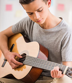 Male teenager sitting at home and playin