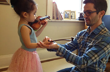 Child and parent practice together at Suzuki violin lesson at Upper Beaches Music School in Danforth, East Toronto