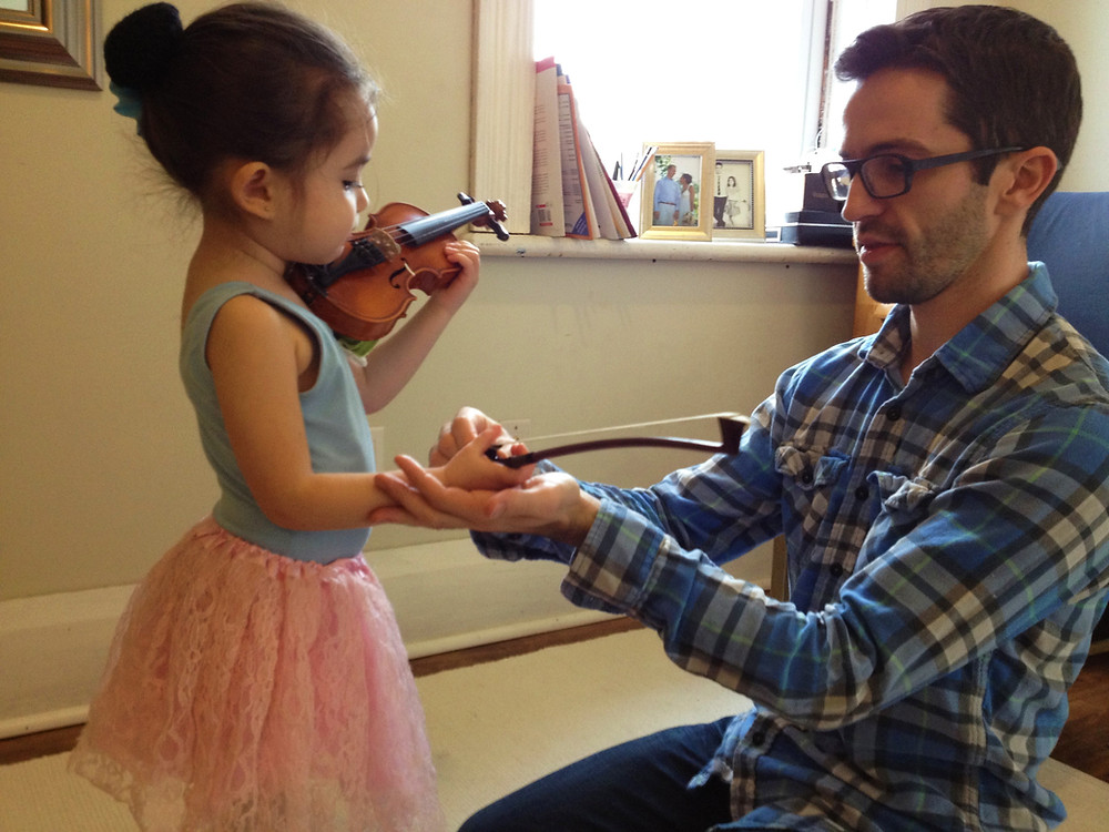 Father practicing violin with his daughter in the Suzuki method violin lesson at Upper Beaches Music School in east Toronto on Danforth