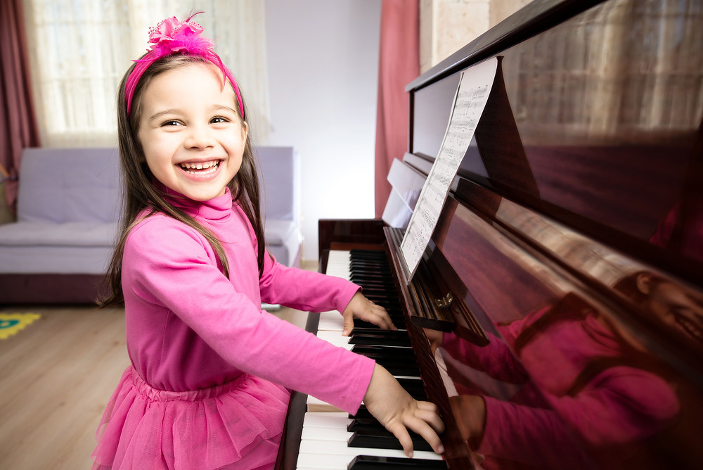 Young girl happily plays the piano at Upper Beaches Music School