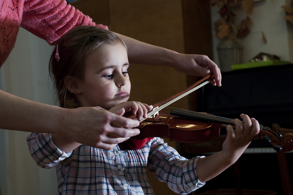 A young girl practices violin at home with her parents.