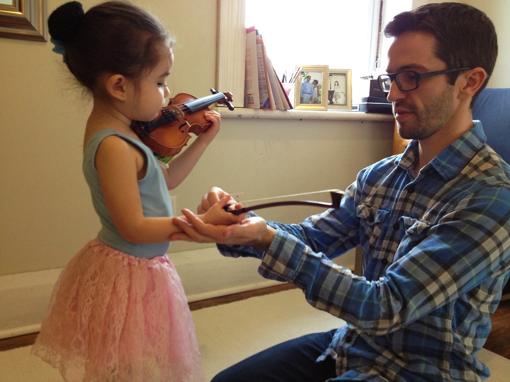 A father practices violin at home with his daughter