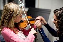 Adult plays fiddle in group music class at Upper Beaches Music School in East Toronto on Danforth