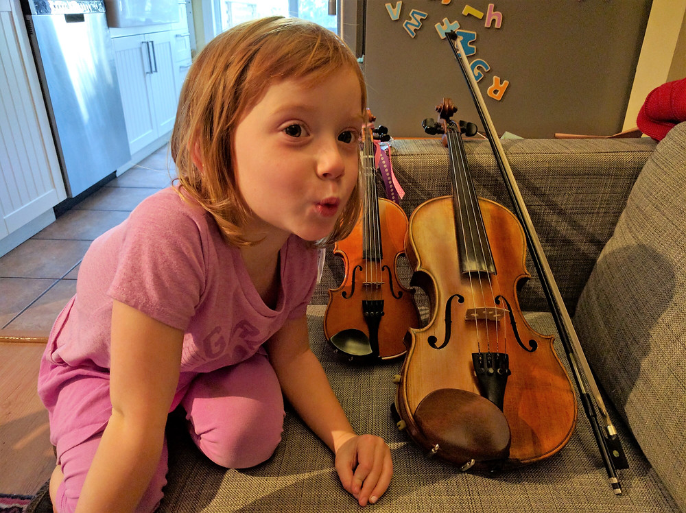 Young girl gets ready to practice violin.