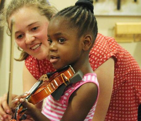 Child and teacher play violin at Suzuki music lesson at Upper Beaches Music School in Danforth, East Toronto