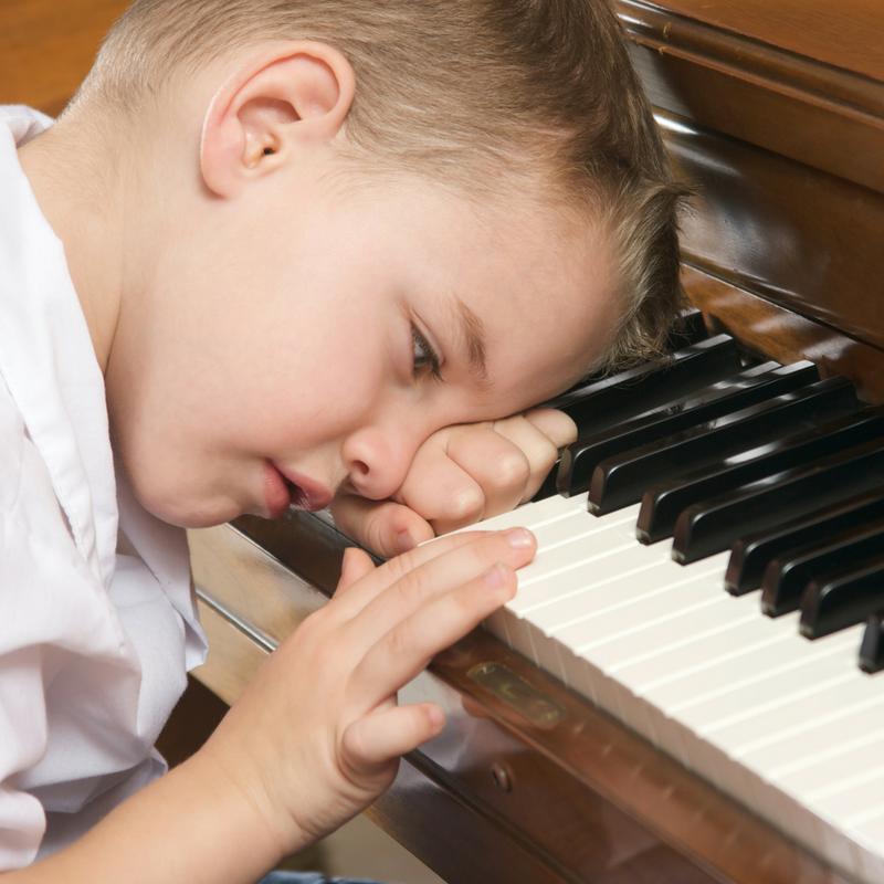 Young boy dreaming at the piano