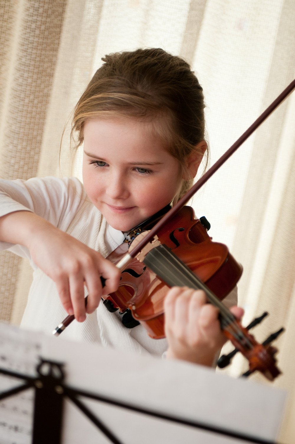 Young child plays violin with music at music lesson at Upper Beaches Music School in East Toronto on Danforth