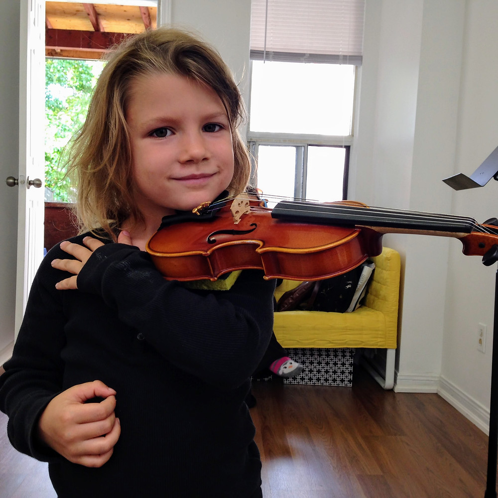 Young child plays violin at music lesson at Upper Beaches Music School in east Toronto on danforth
