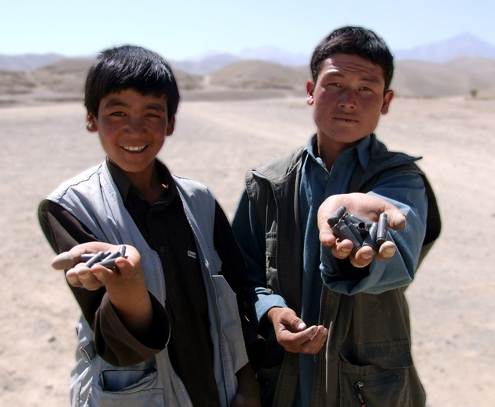 Two Afghan boys hold the bullet shells they have gathered and will now sell for scrap value to buy food.